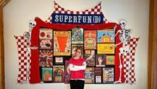 Artist Maggy Rozycki Hiltner, in from of her Superfund quilt.