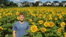 Blake Gunter standing in his Sunflower Field