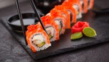 A sushi roll laid out on a black slate