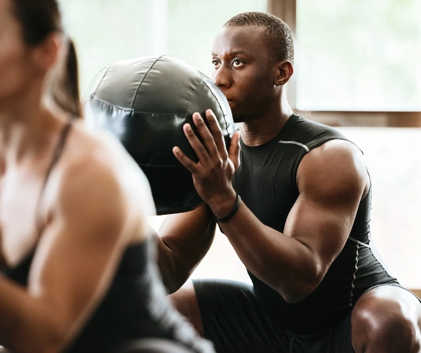 Gym member doing a high intensity workout with ball.