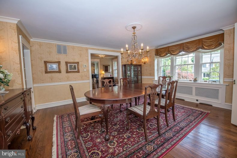 Dining room table and chairs over carpet.