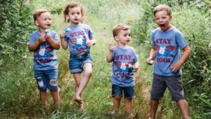 four kids outside in grass.