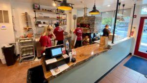 Staff at Terra Nova Woodfired Pizza & Grill working on a Hawaiian Pizza