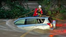 A motorist is helped by a first responder in a water rescue from flood waters along Valley Creek.