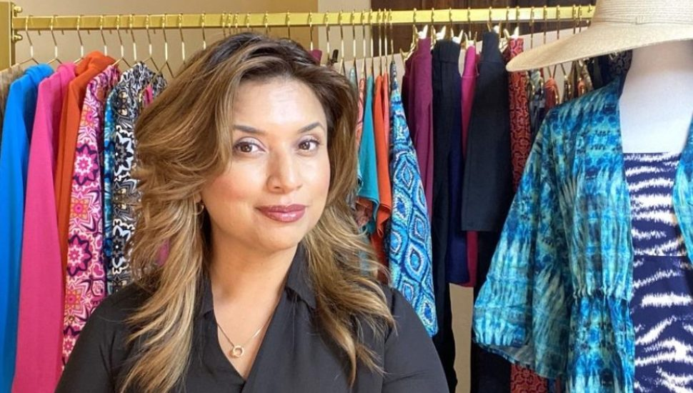 woman in front of rack of clothes