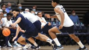 Caleb Daniels (left) dives for a loose ball in front of Jermaine Samuels during an Oct. 7 basketball game.