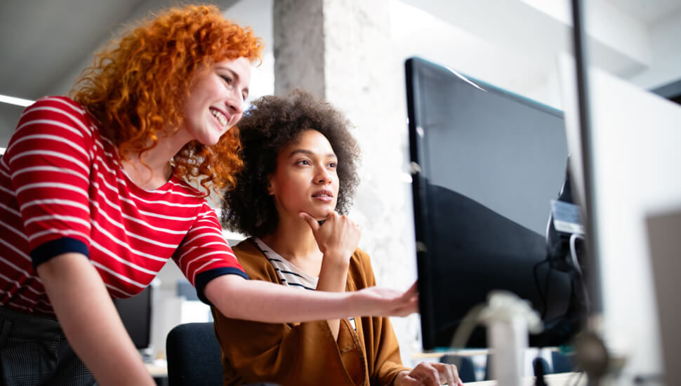 Two Women looking at a computer monitor
