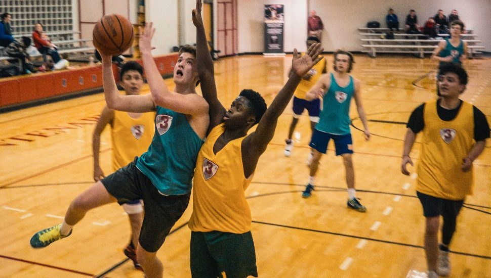 Boys playing basketball in high school.